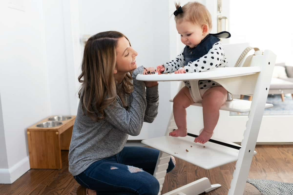 Baby and mom at high chair starting solid food