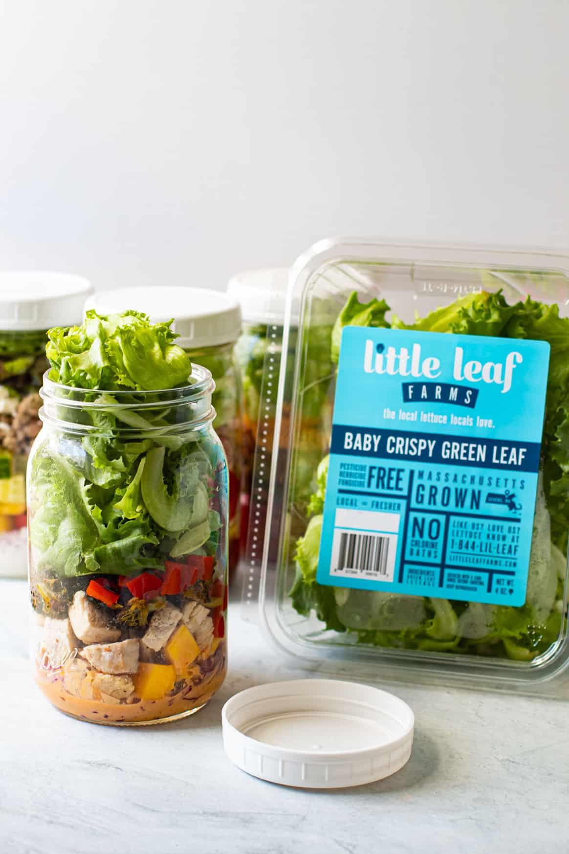 Mason jar salads next to a box of lettuce.