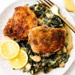 A plate with crispy chicken thighs and lemon greens.