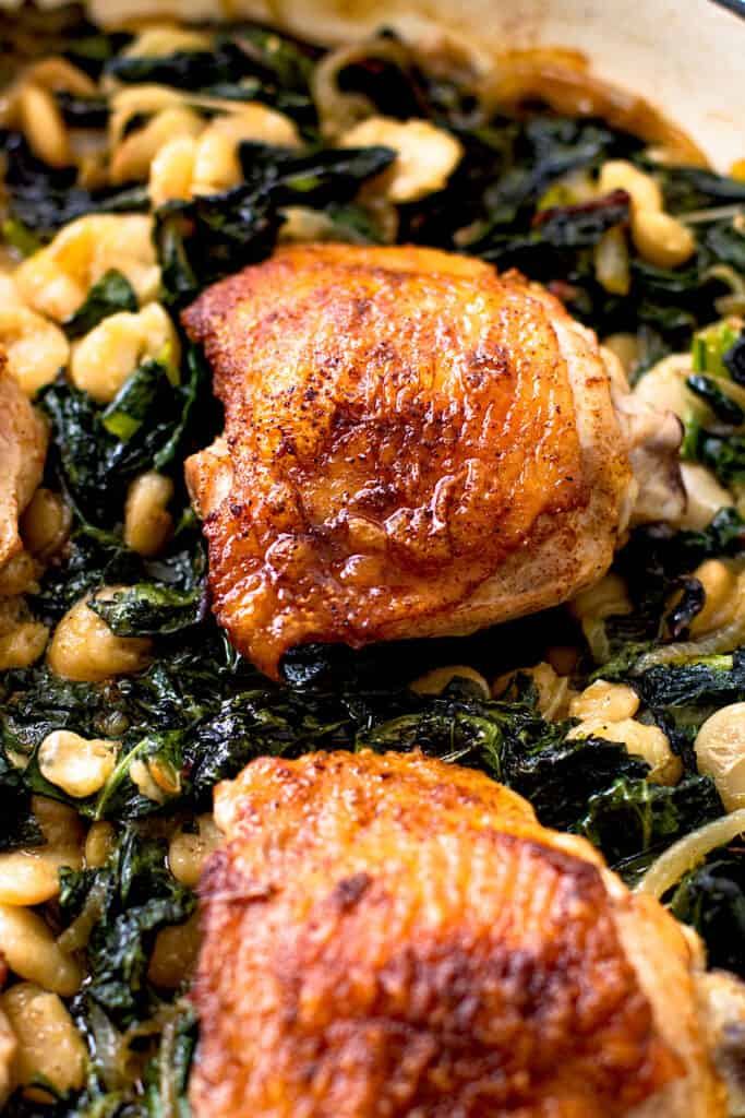 An oven proof skillet with crispy chicken thighs and greens.