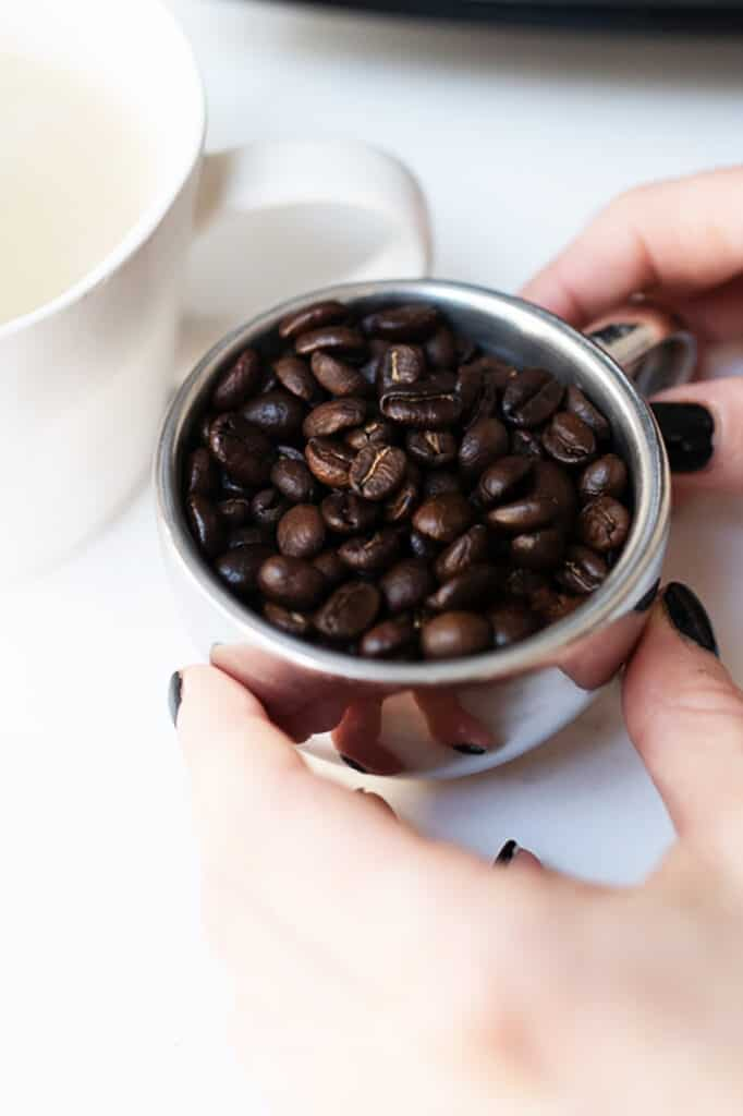 A small cup for of coffee beans.