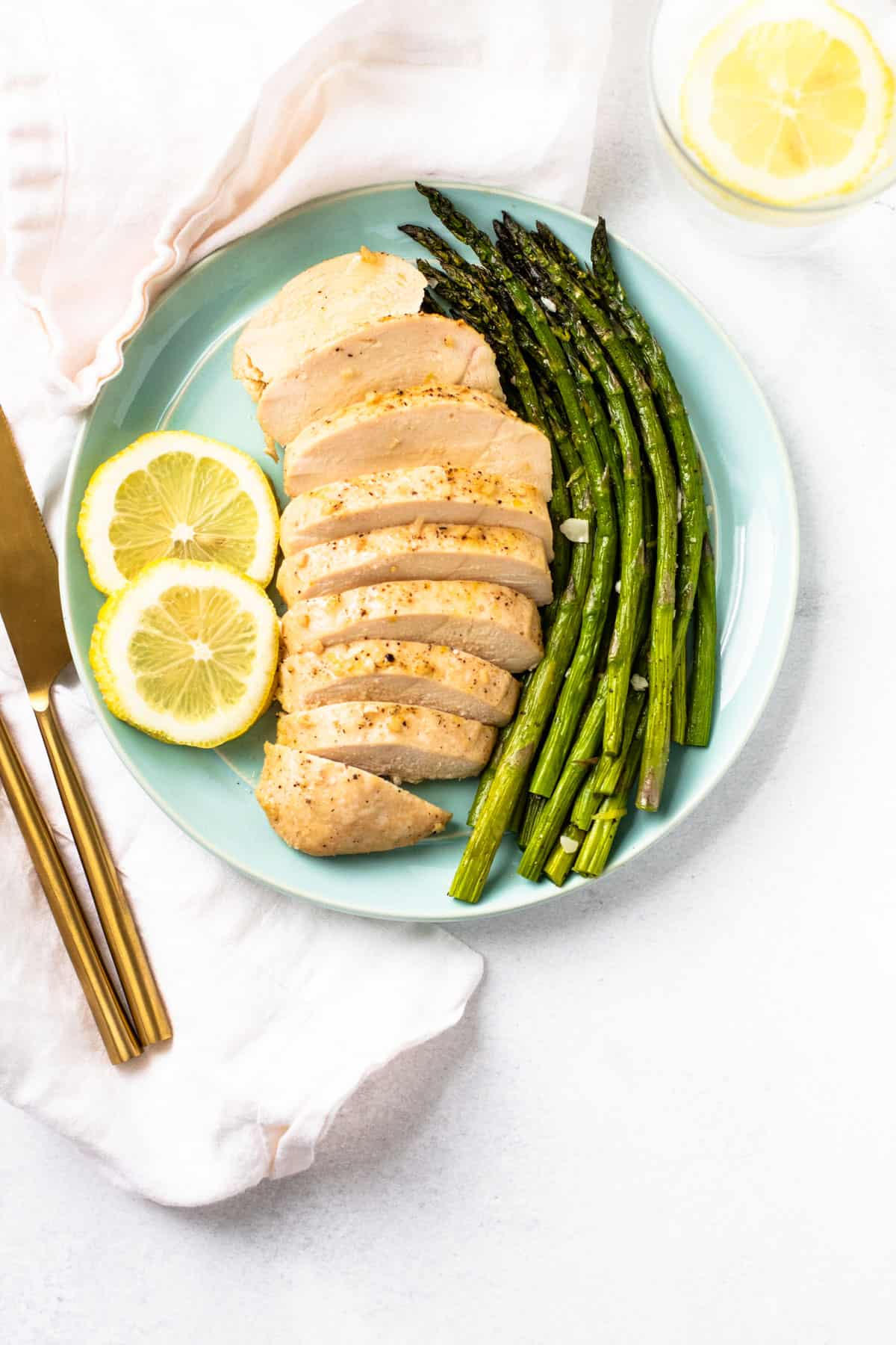 Air fryer asparagus served with a dish of chicken.