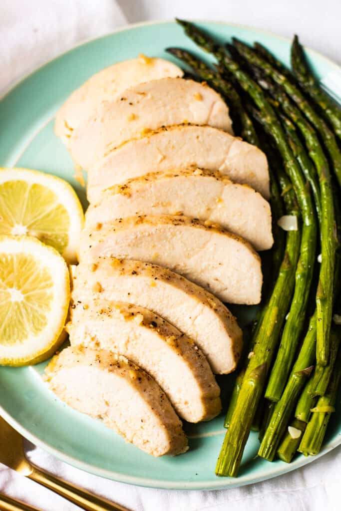 Lemon pepper baked chicken on a plate with asparagus.