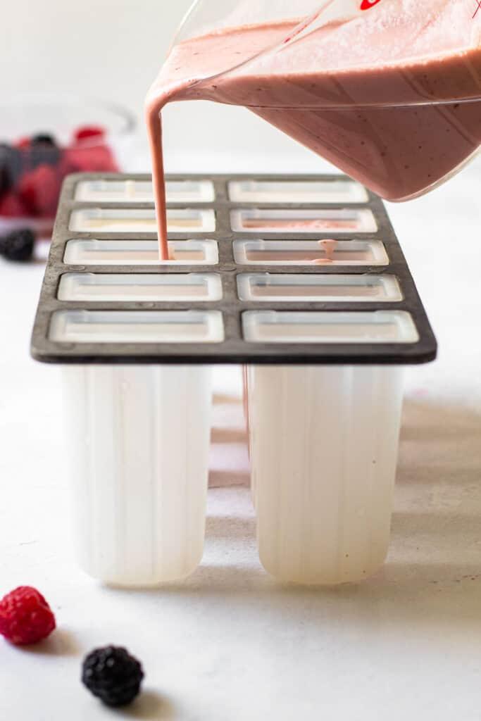 Pouring greek yogurt popsicles into molds.