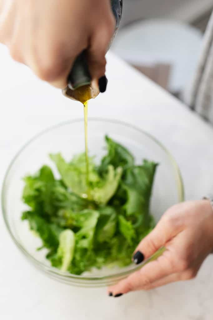 A bottle of olive oil being poured into a salad.