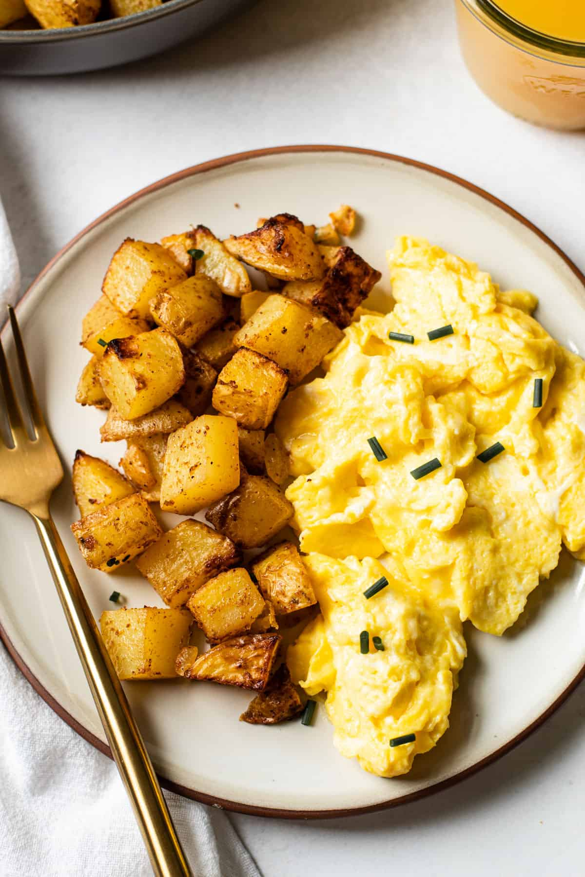A plate of air fryer home fries with scrambled eggs.