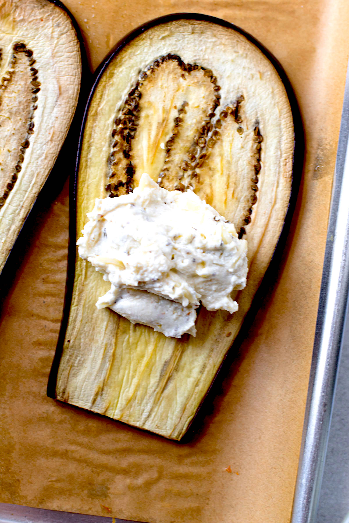 A baked eggplant with a scoop of ricotta cheese.