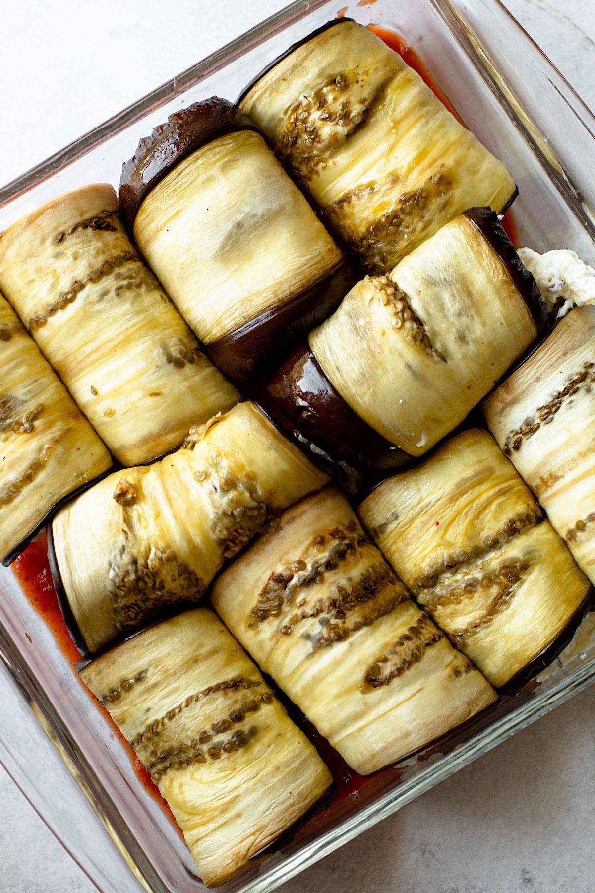 Eggplant rollatini inside of a baking dish.
