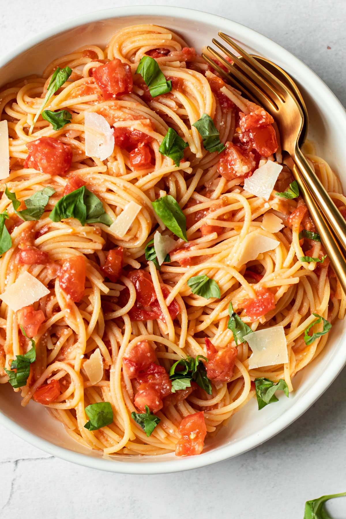 Fresh tomato pasta in a bowl with basil.