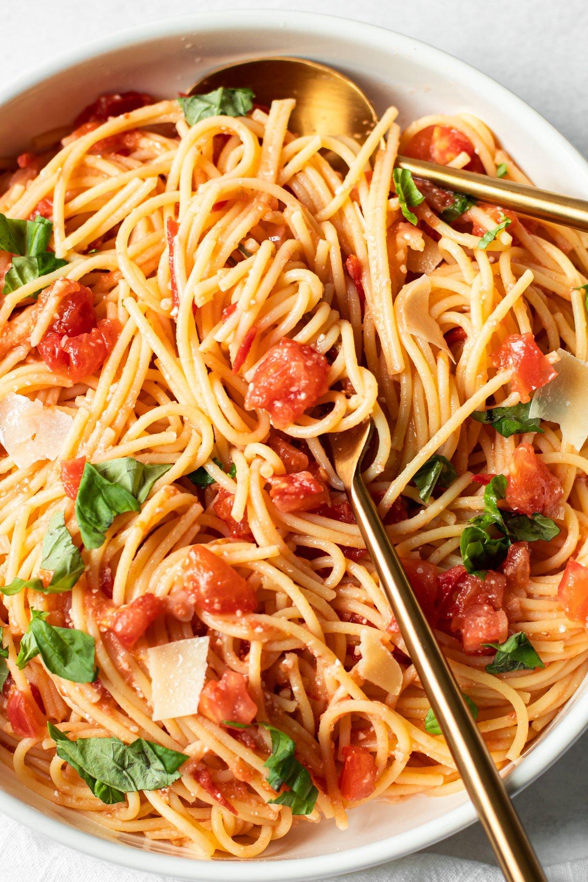 A bowl of fresh tomato spaghetti with basil.