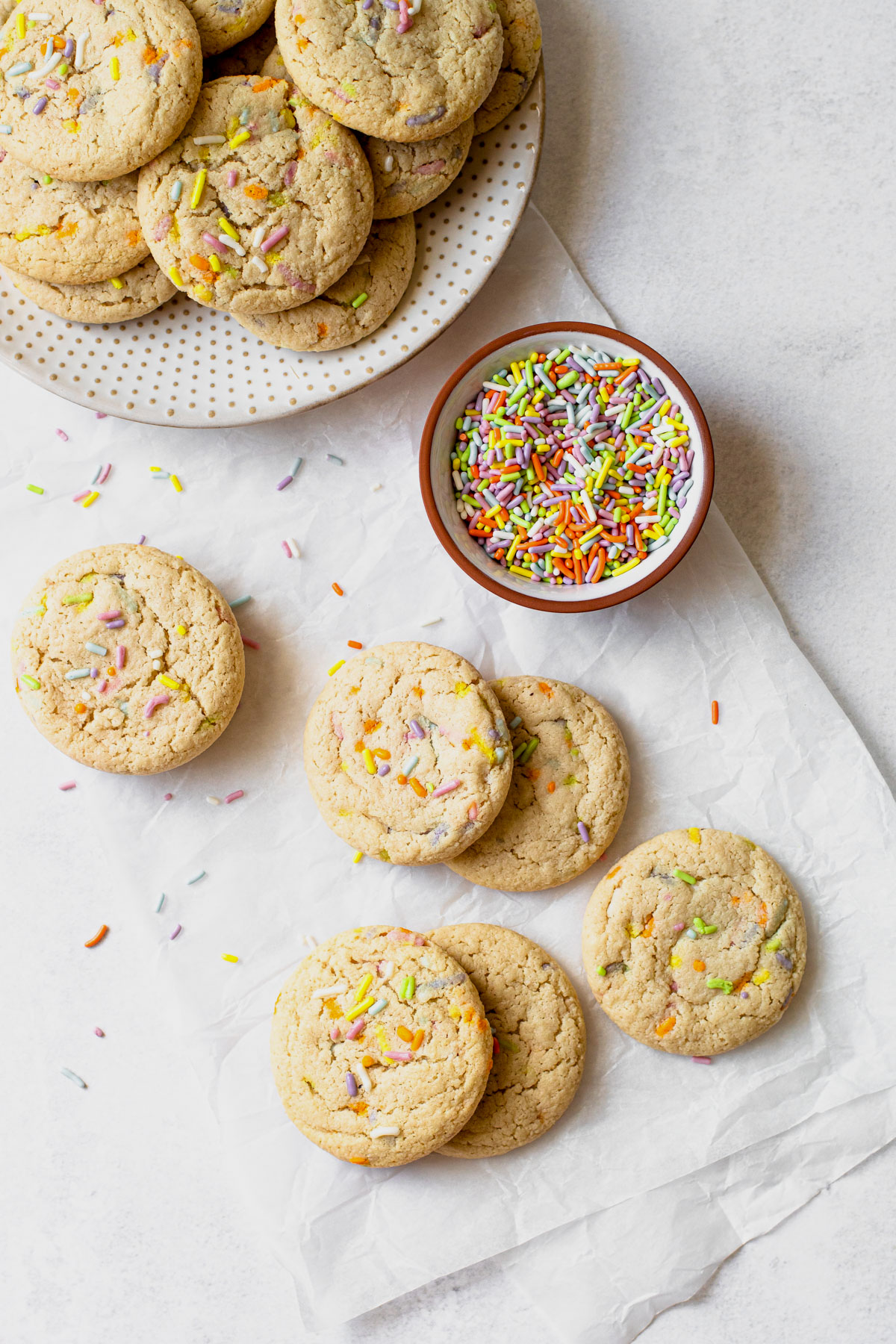 Funfetti sugar cookies next to a bowl of sprinkles.
