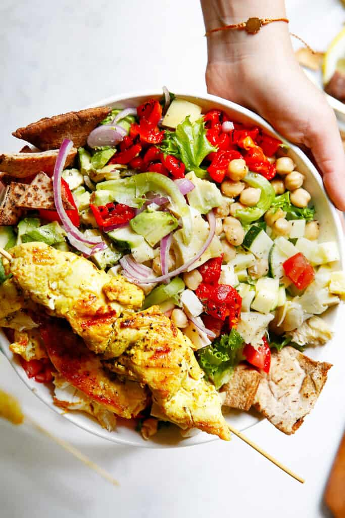 Chicken kebabs on a plate with greek salad.