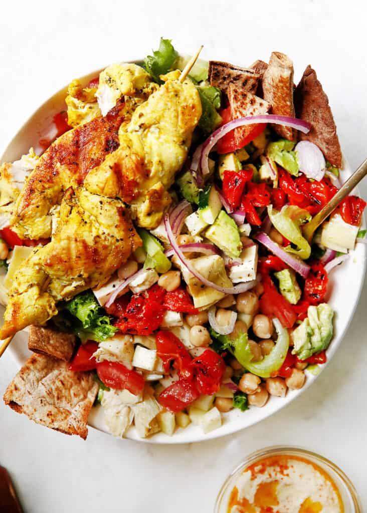 Grilled greek chicken kebabs over a bed of greek dressing.
