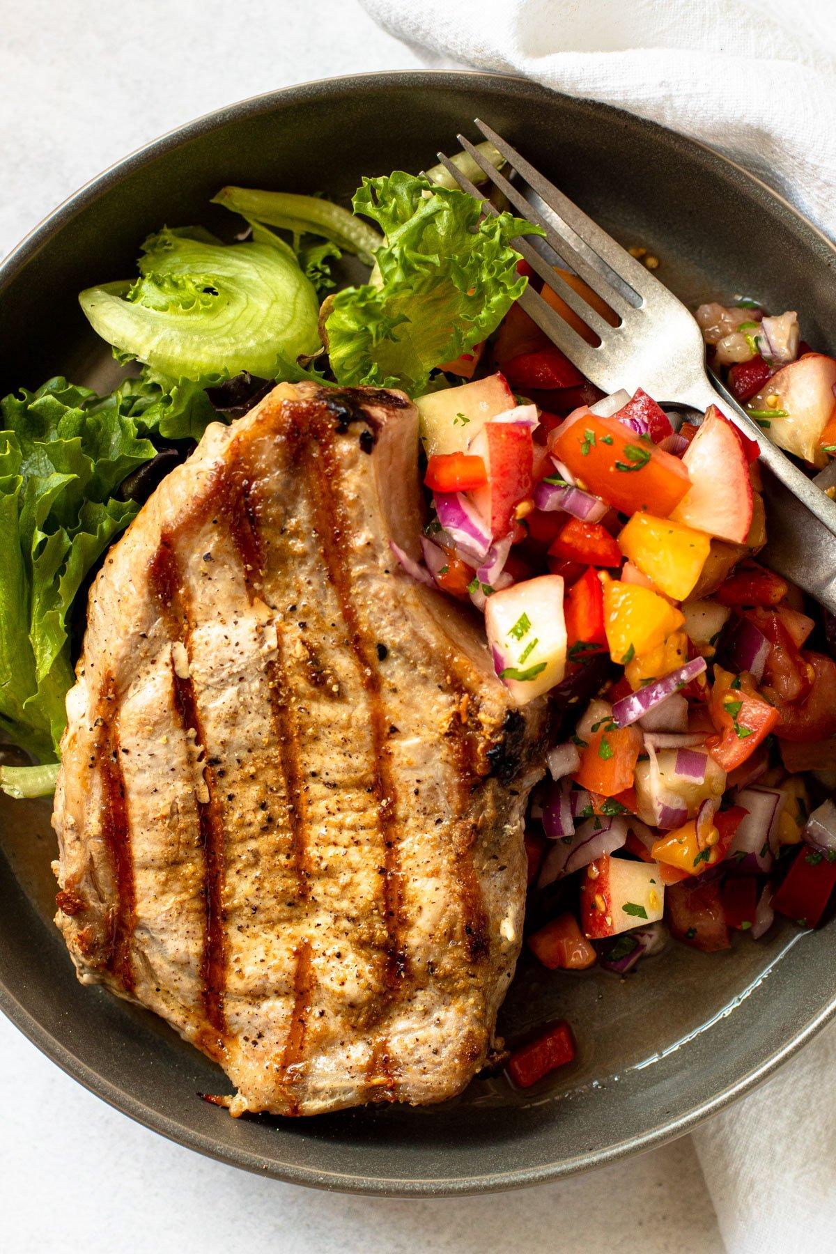 Grilled pork chop with peach salsa.