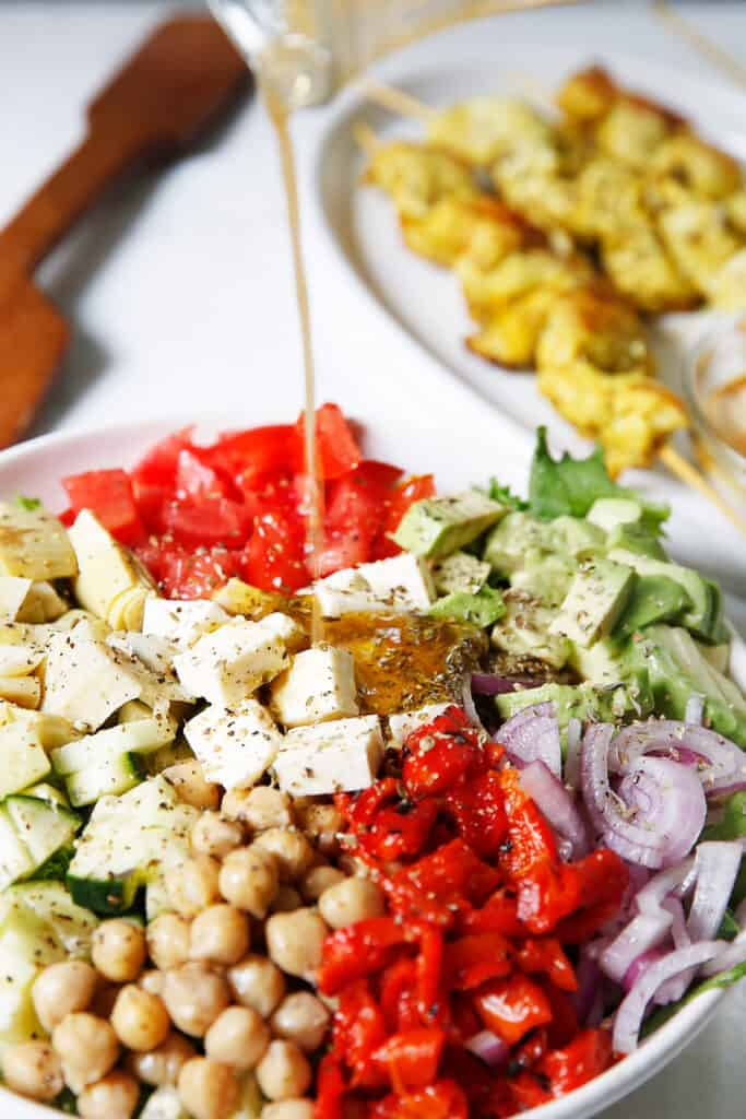 Greek salad with dressing being poured onto it