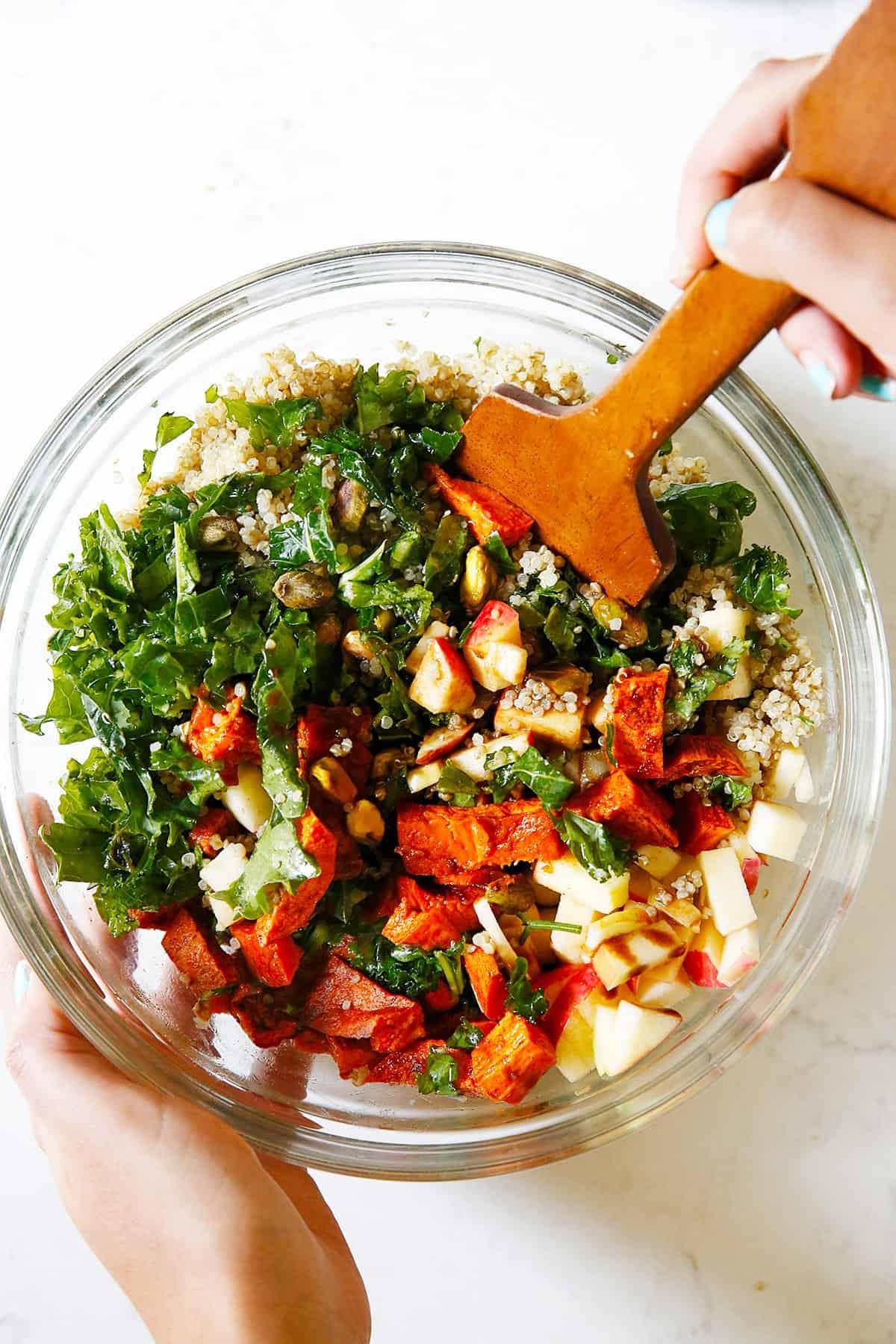 Mixing together a sweet potato quinoa salad