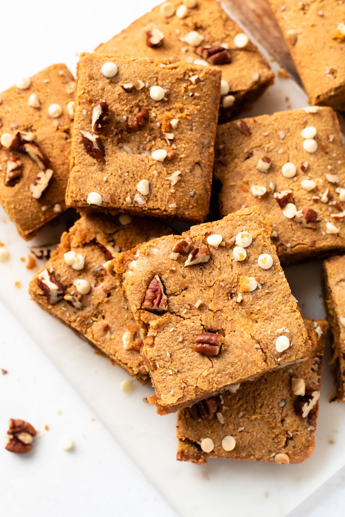 A stack of gluten-free blondies with white chocolate and pecans.