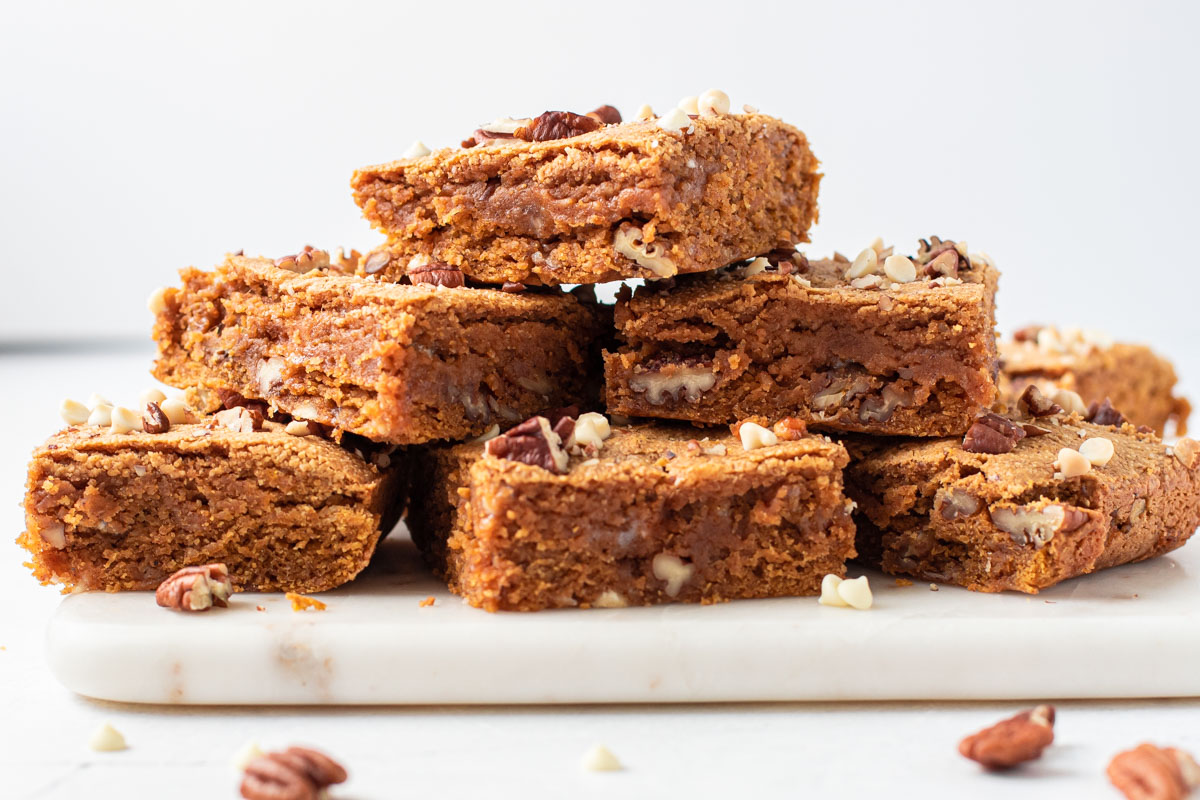 Pumpkin spice blondies stacked up on a tray.