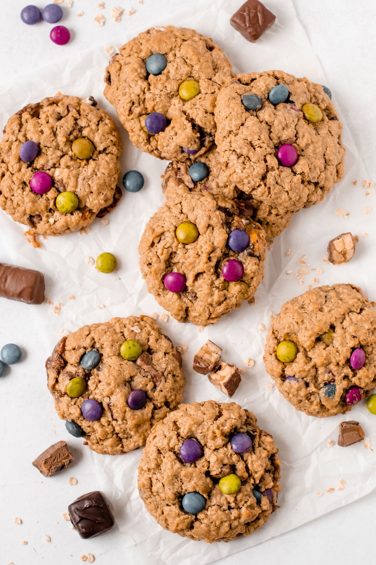 Gluten free monster cookies on a piece of parchment paper surrounded by chopped leftover candy bars.